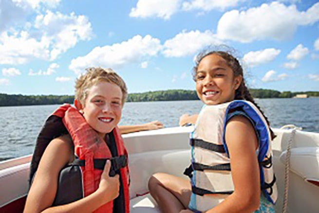 2 kids sitting on a boat smiling - kolter homes lifetyle